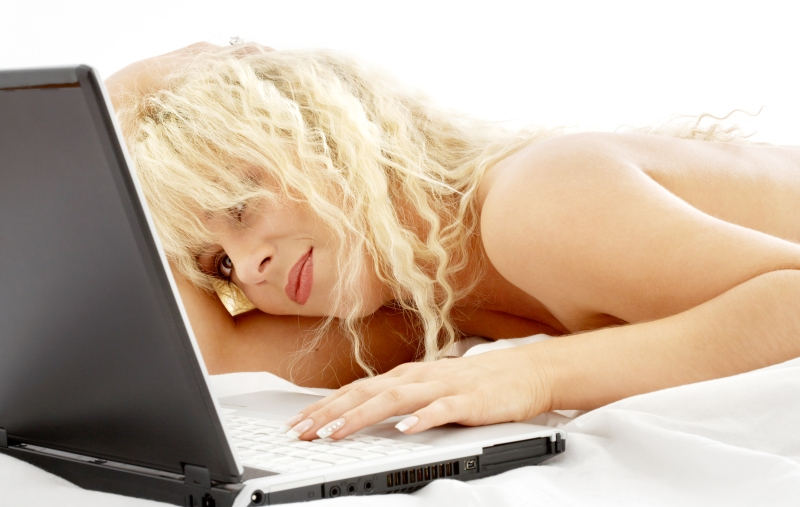 portrait of blond laying in bed with laptop